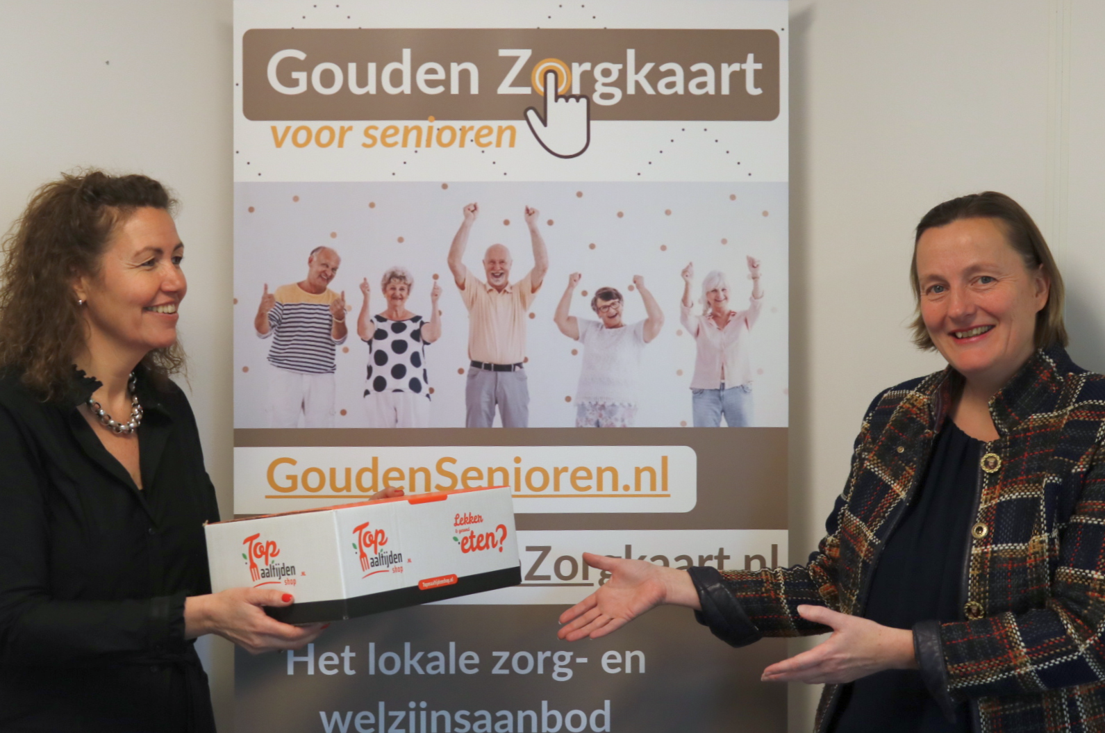 Joke Beekman, directeur TopMaaltijdenShop overhandigt maaltijdenbox aan Vera Verburgt, directeur Gouden Zorgkaart Nederland